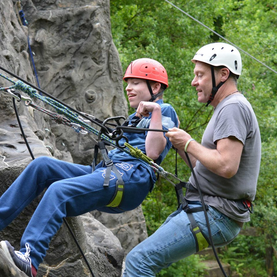 Two males abseiling down a wall with harnesses and safety equipment as a group activity at Calvert Trust Exmoor
