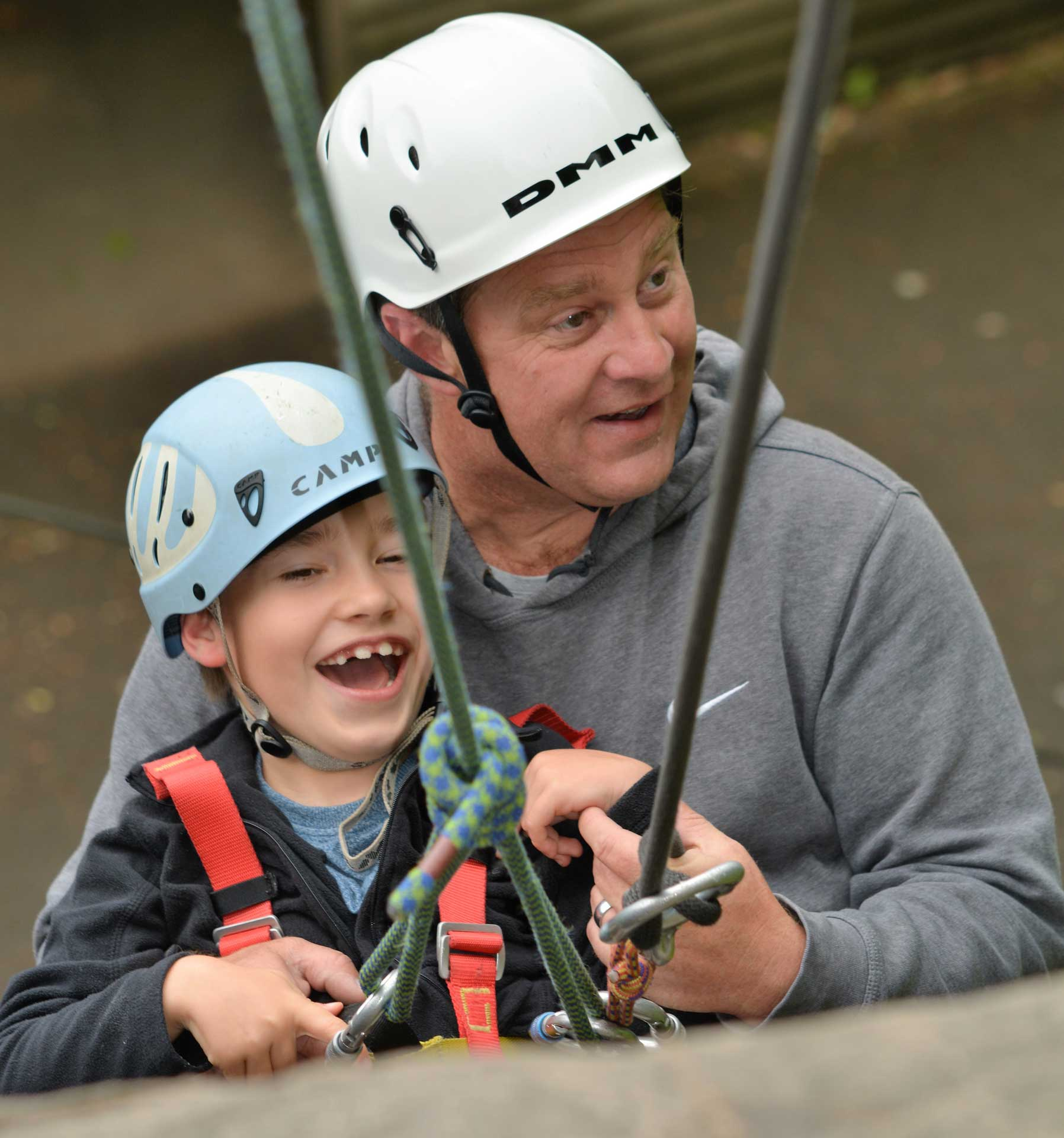 A child and man looking happy abseiling together outside with safety ropes and equipment at Calvert Trust Exmoor