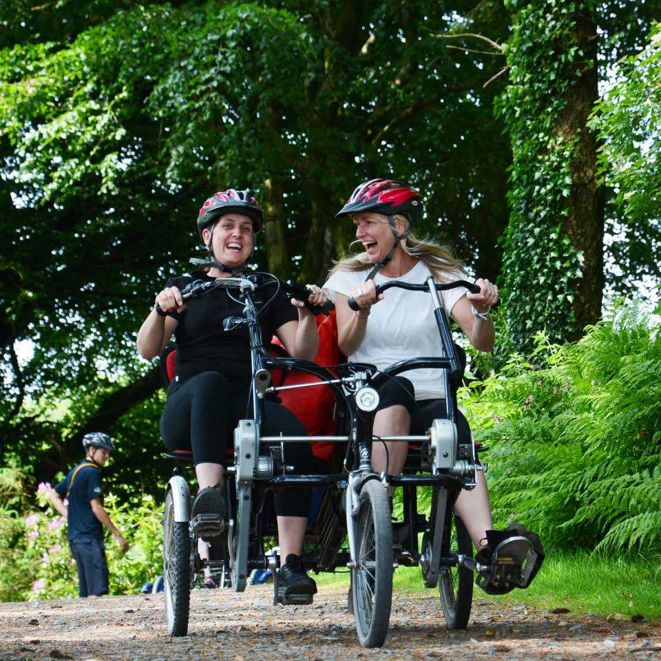 Two female Calvert Trust Exmoor guests laughing whilst cycling on a specialist side by side tandem bike in a wooded area