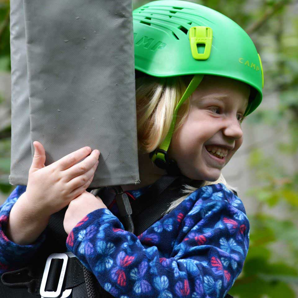 A smiling girl in a green helmet holding onto her harness during a zipline activity at Calvert Trust Exmoor
