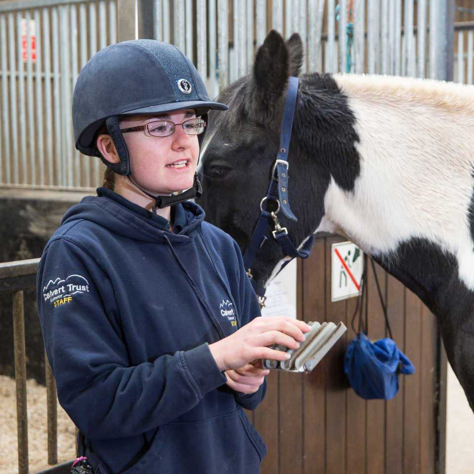 Calvert Trust Exmoor stable instructor wearing riding helmet, next to a brown and white horse, holding a grooming brush and talking