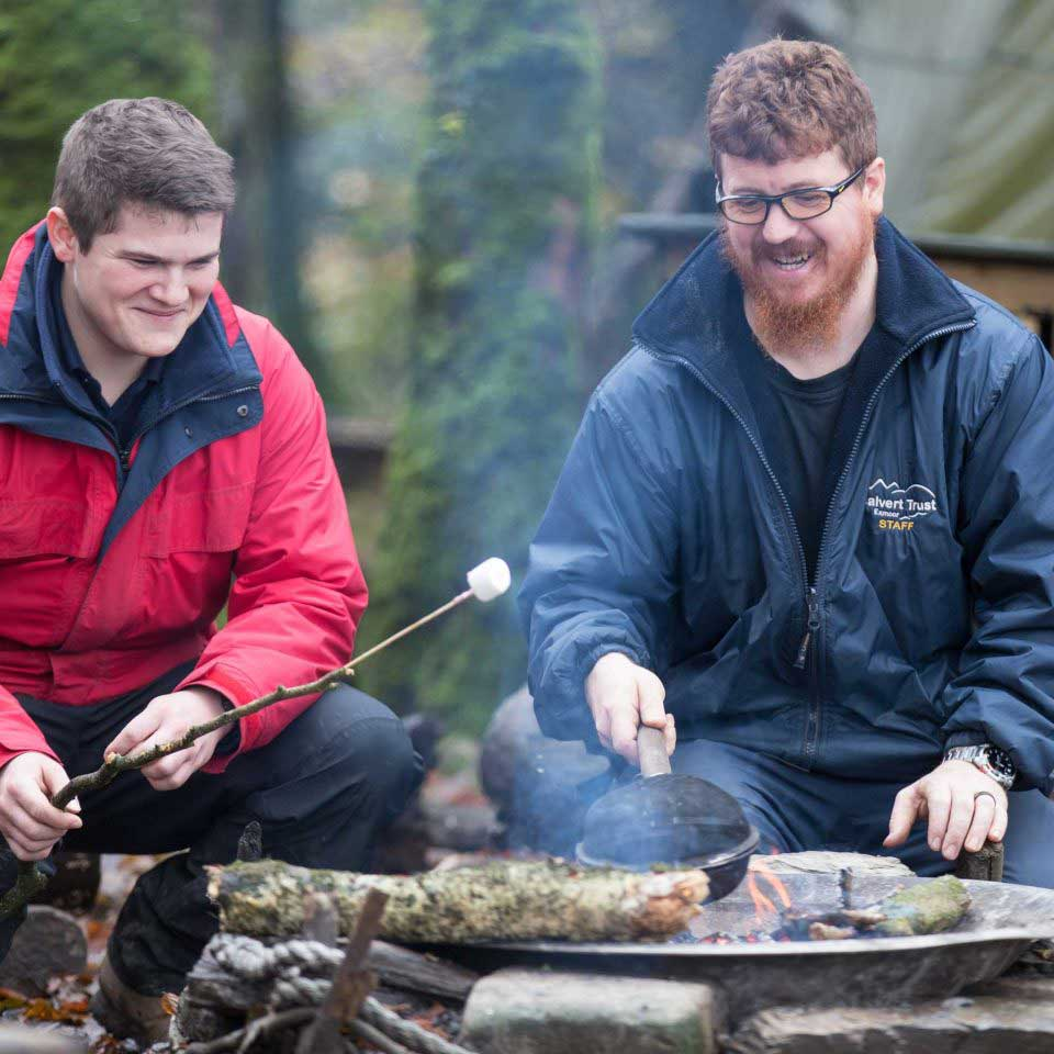 Two male Calvert Trust Exmoor activities instructors outside cooking marshmallows and popcorn over an open fire, smiling