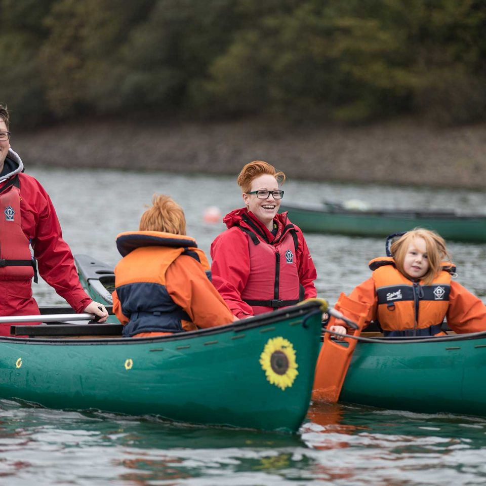Smiling family in tandem canoes on water at Calvert Trust Exmoor wearing lifejackets
