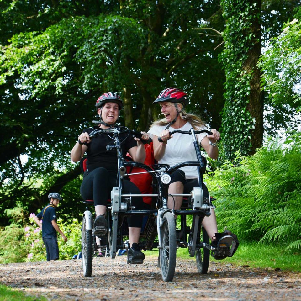 Two Calvert Trust Exmoor guests laughing whilst cycling on a tandem bike in a wooded area