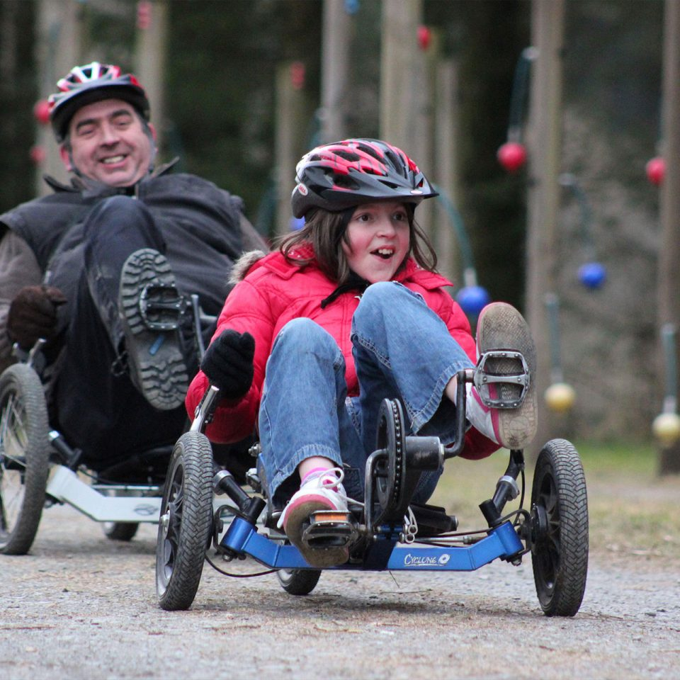 Girl and man on accessible bikes along a track at Calvert Trust Exmoor