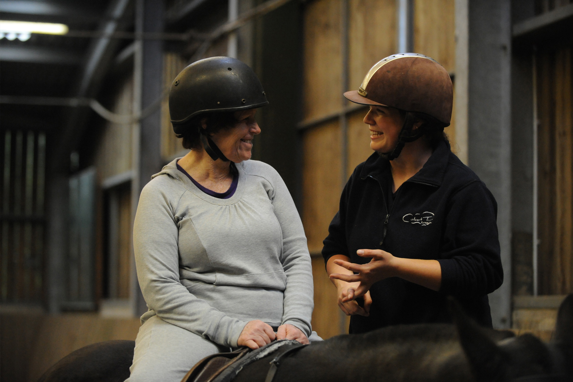 A lady sat on top of a black horse chatting to a member of the Calvert Trust stables volunteer team in the indoor arena, both smiling