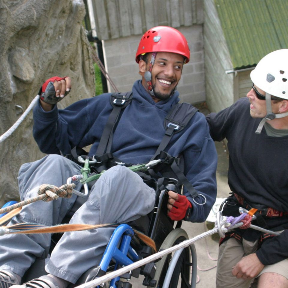 A man in a wheelchair abseiling down a wall with ropes and an instructor