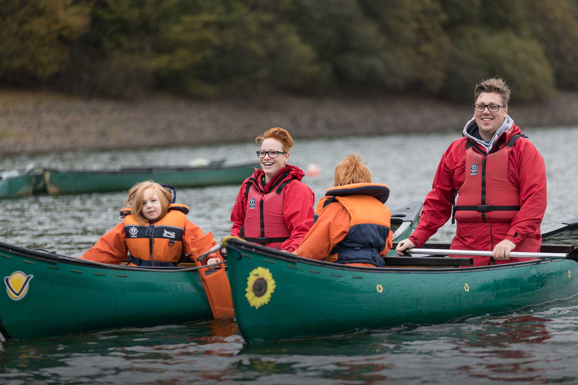 Young family of four wearing life jackets in rafted canoes on the water at Calvert Trust Exmoor, with paddles