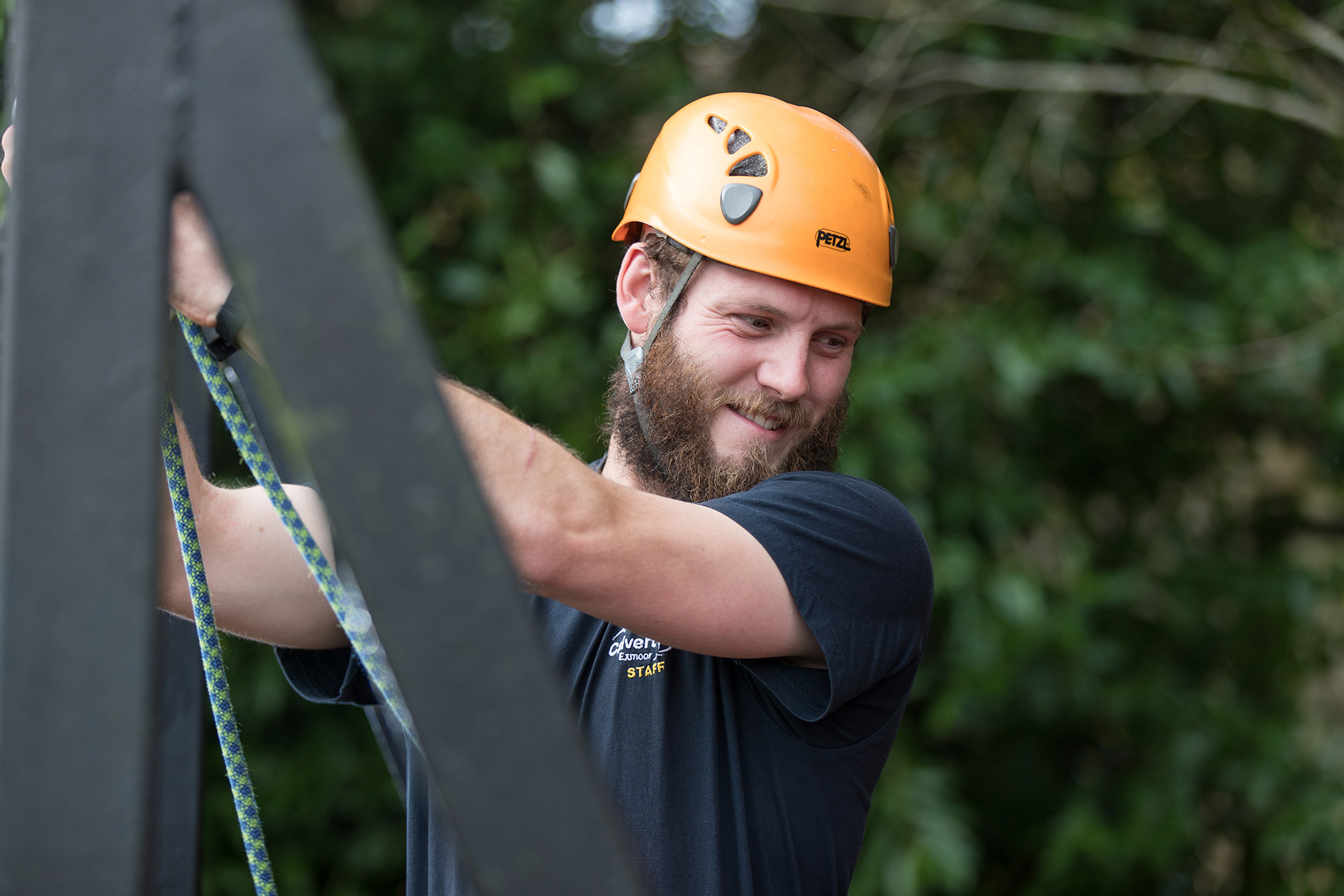 Smiling Calvert Trust Exmoor activities instructor with ropes wearing a helmet