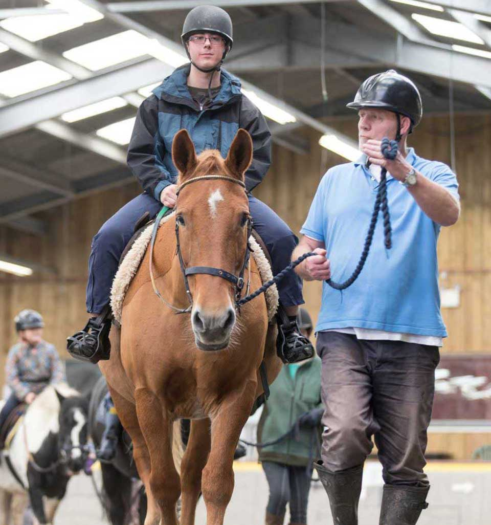 A young man riding a red brown horse in the indoor arena, being led by a stables volunteer at Calvert Trust Exmoor