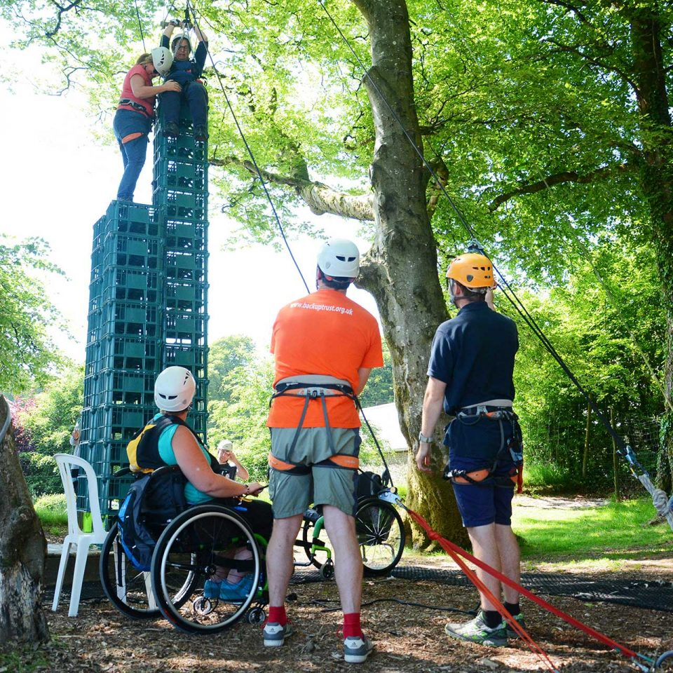 Two people on top of a stack of crates with harnesses outside amongst trees, being watched on by others including two in wheelchairs
