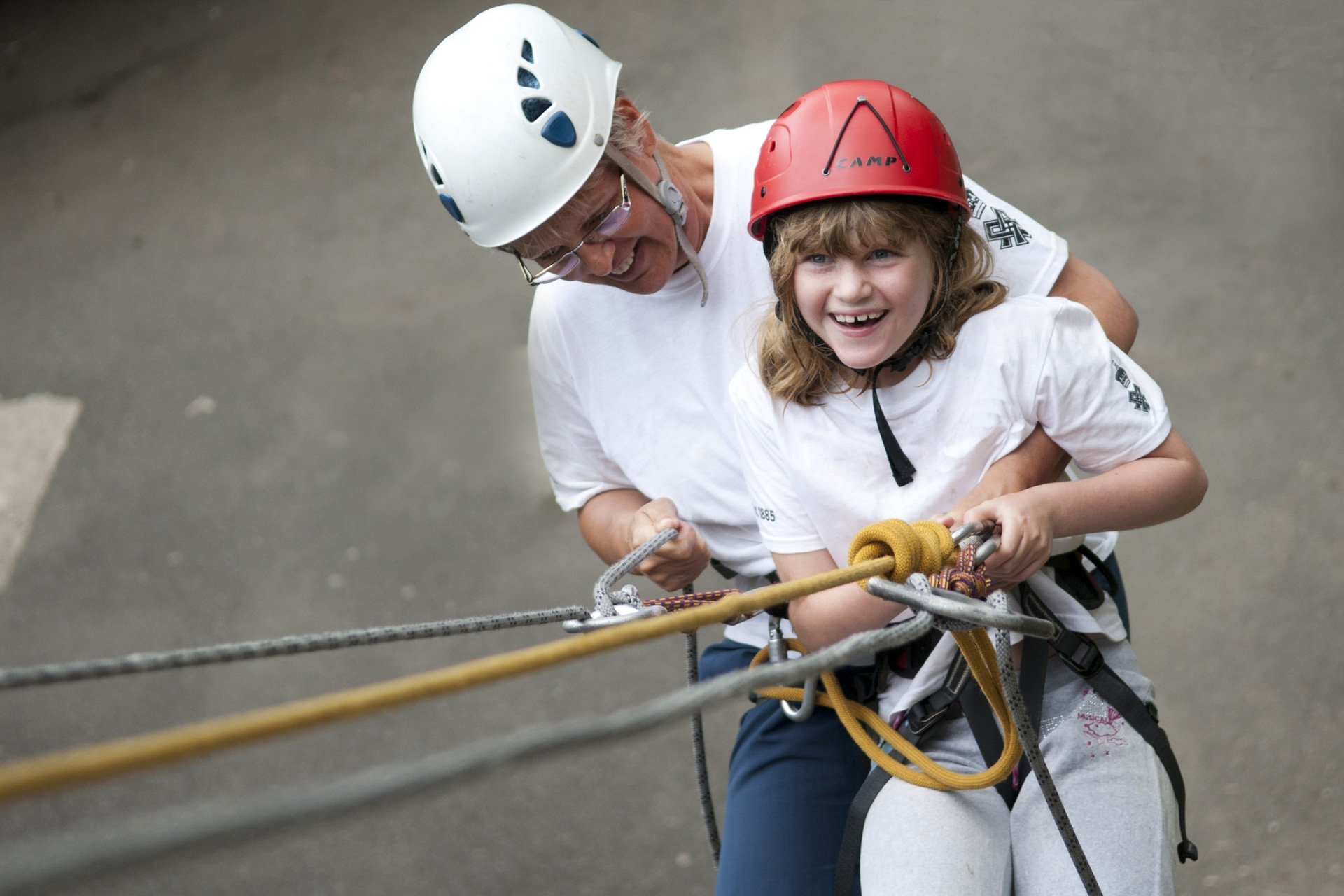 Girl and lady tandem abseiling down outdoor climbing wall at Calvert Trust Exmoor with safety ropes, harnesses and helmets