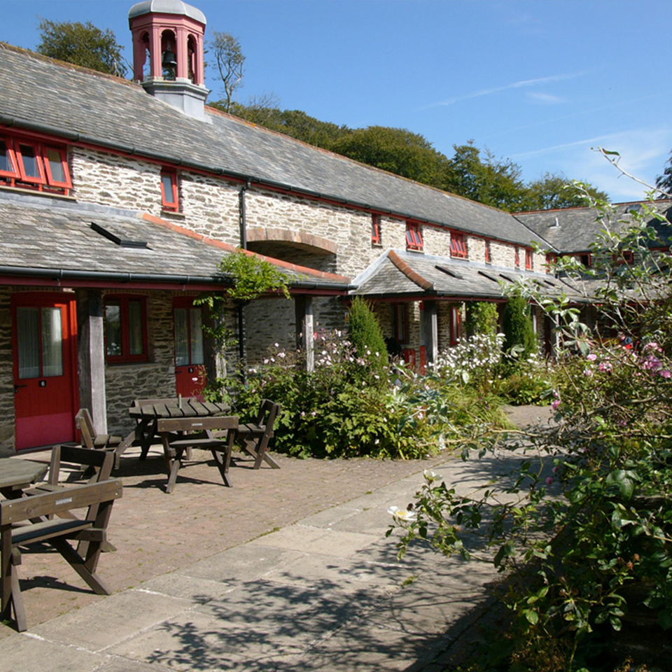 View of stone accommodation building with wooden picnic tables, plants and bushes, and blue sky
