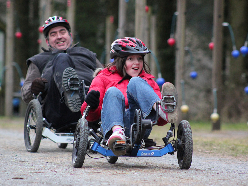 A girl and a man riding accessible recumbent bikes along an outdoor track