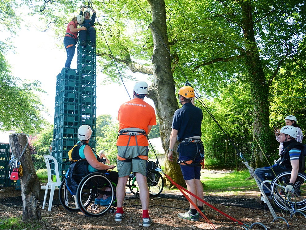 Two women on top of a stack of crates amongst trees, being watched by a group of people, some in wheelchairs, all with safety harnesses
