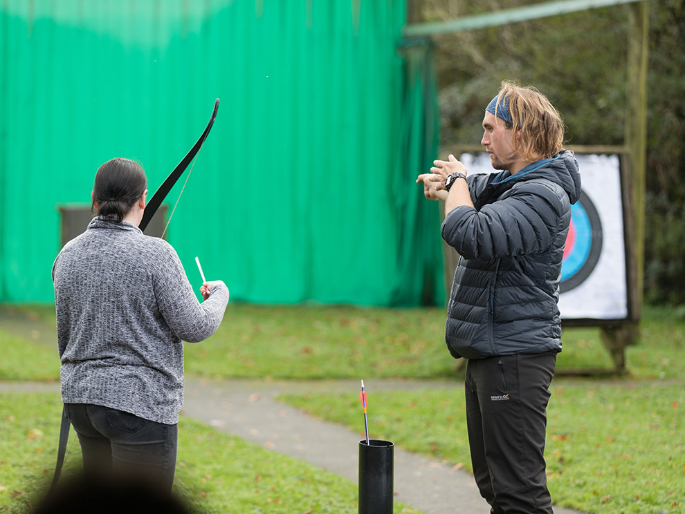 Activity instructor demonstrating archery with a lady holding a bow and arrow