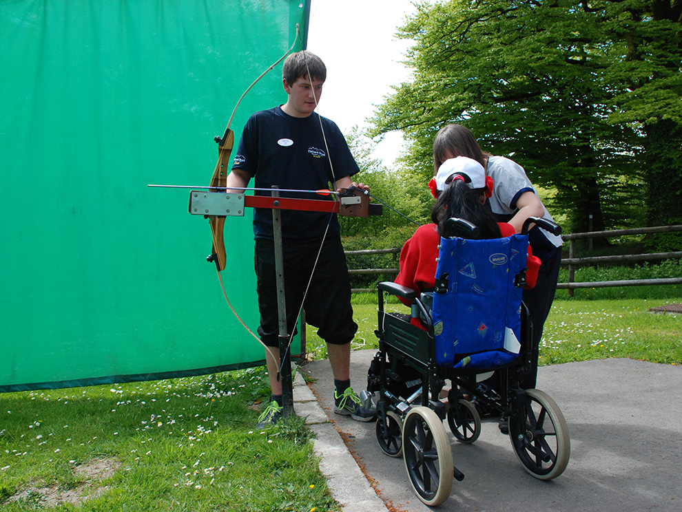 Girl in wheelchair doing archery with activity instructor