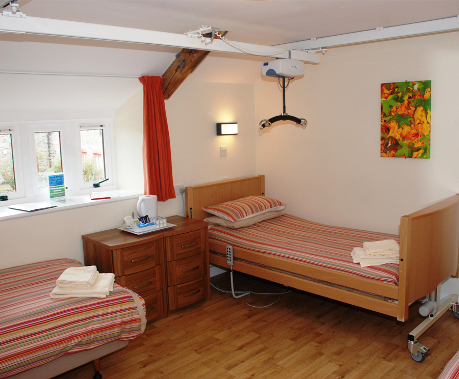 Bedroom with two single beds, ceiling hoist and household essentials