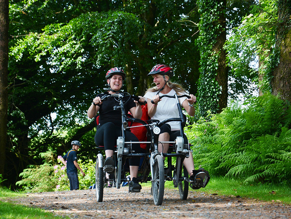 Two laughing ladies on a tandem bike, cycling down a path amongst trees