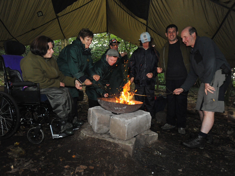 Group of people, one in a wheelchair, around a fire cooking marshmallows in a giant tent