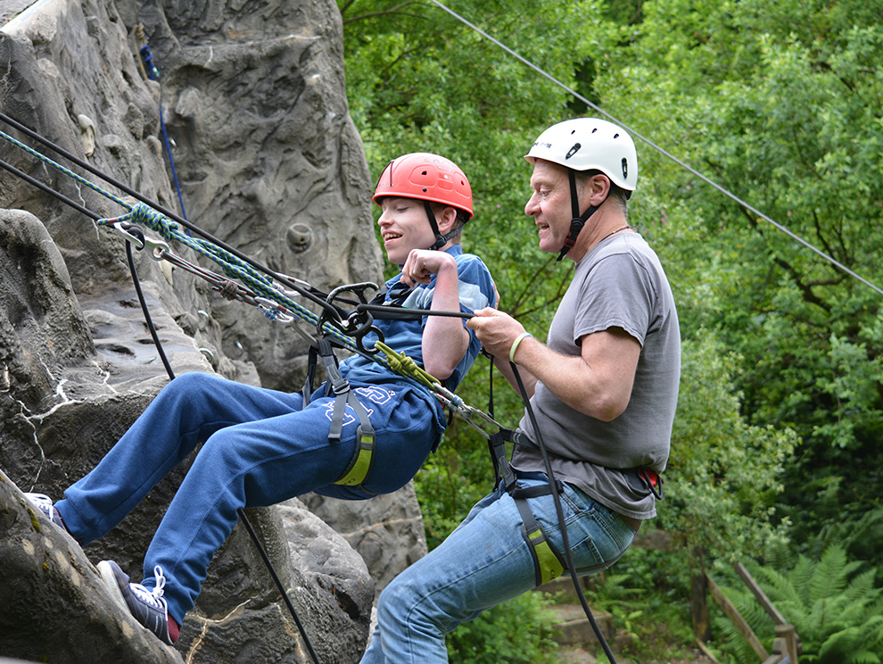 A boy and man abseiling down an outdoor climbing wall with safety equipment and ropes