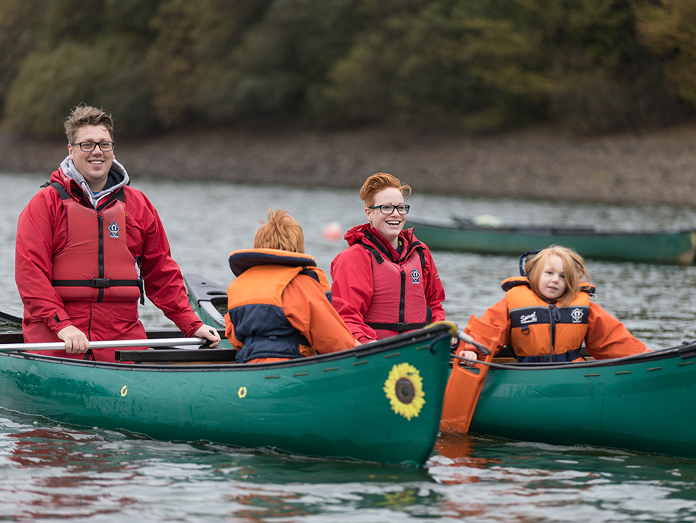 Family wearing lifejackets in rafted canoes on water at Wistlandpound Reservoir