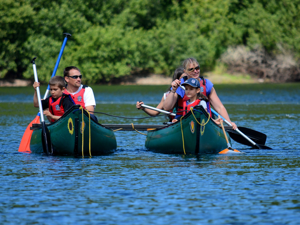 Family wearing life jackets canoeing through water on tandem rafted canoes