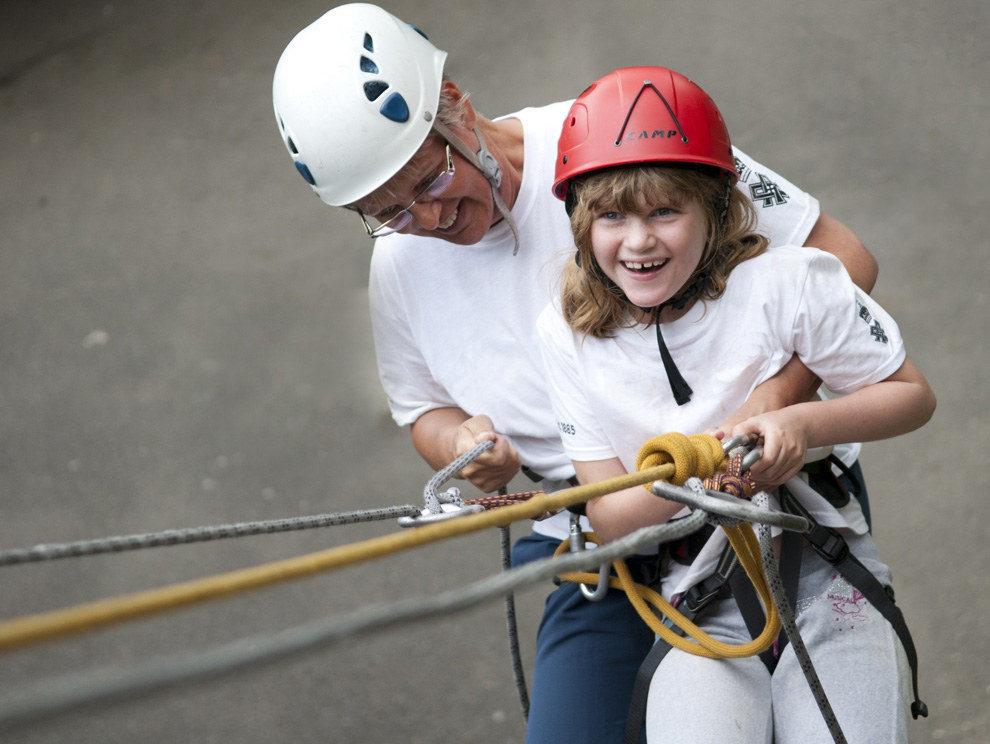 Young girl tandem abseiling with help of a lady and harness equipment, looking back up the wall
