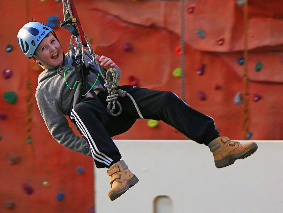 Boy in a harness on a secure rope smiling and swinging freely with orange indoor climbing wall behind