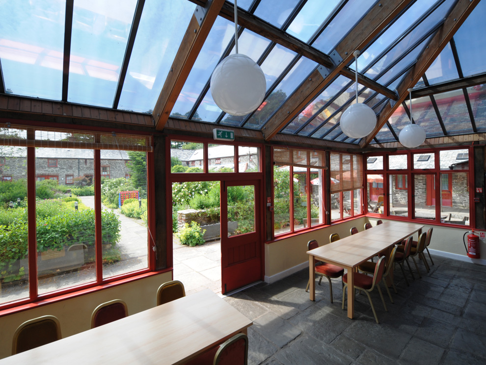 A large conservatory filled with tables and chairs with views of a courtyard with bushes and flowers