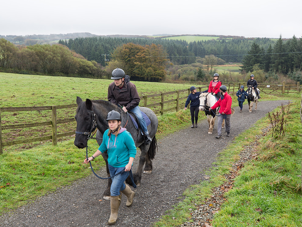 Line of horses and riders being led up a path through fields in the countryside