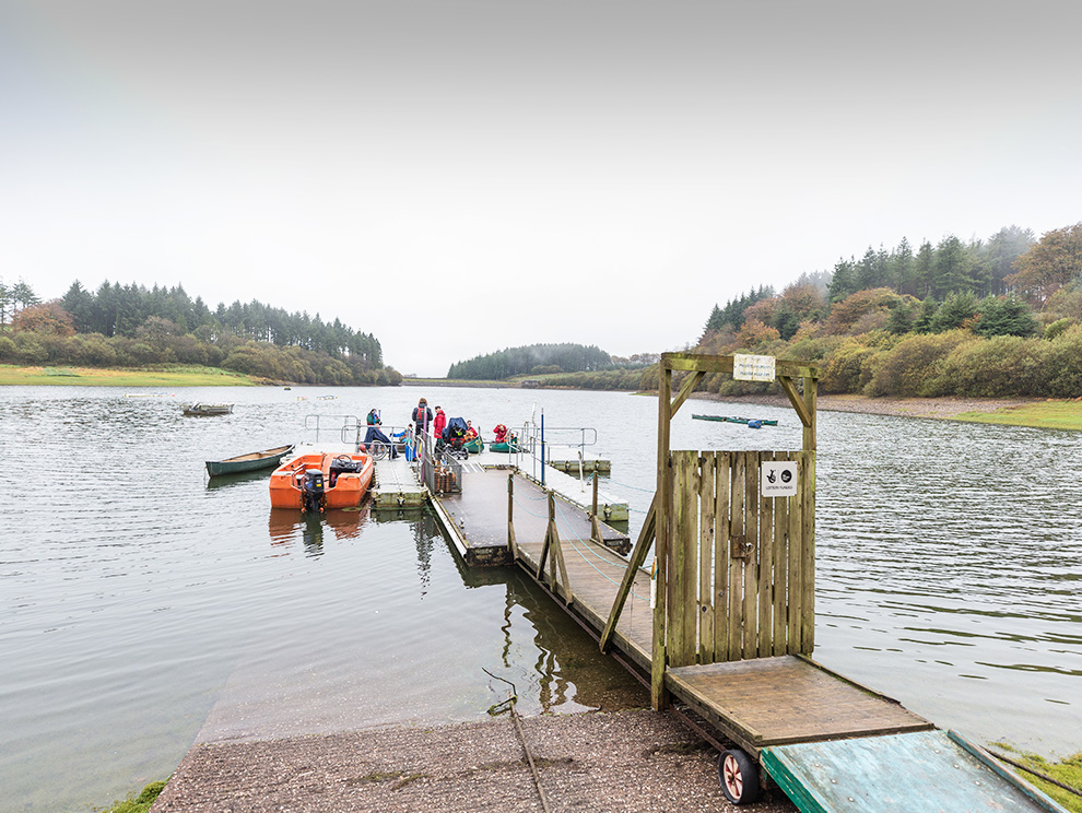 Jetty with door joining land and pontoon in reservoir with people getting into canoes