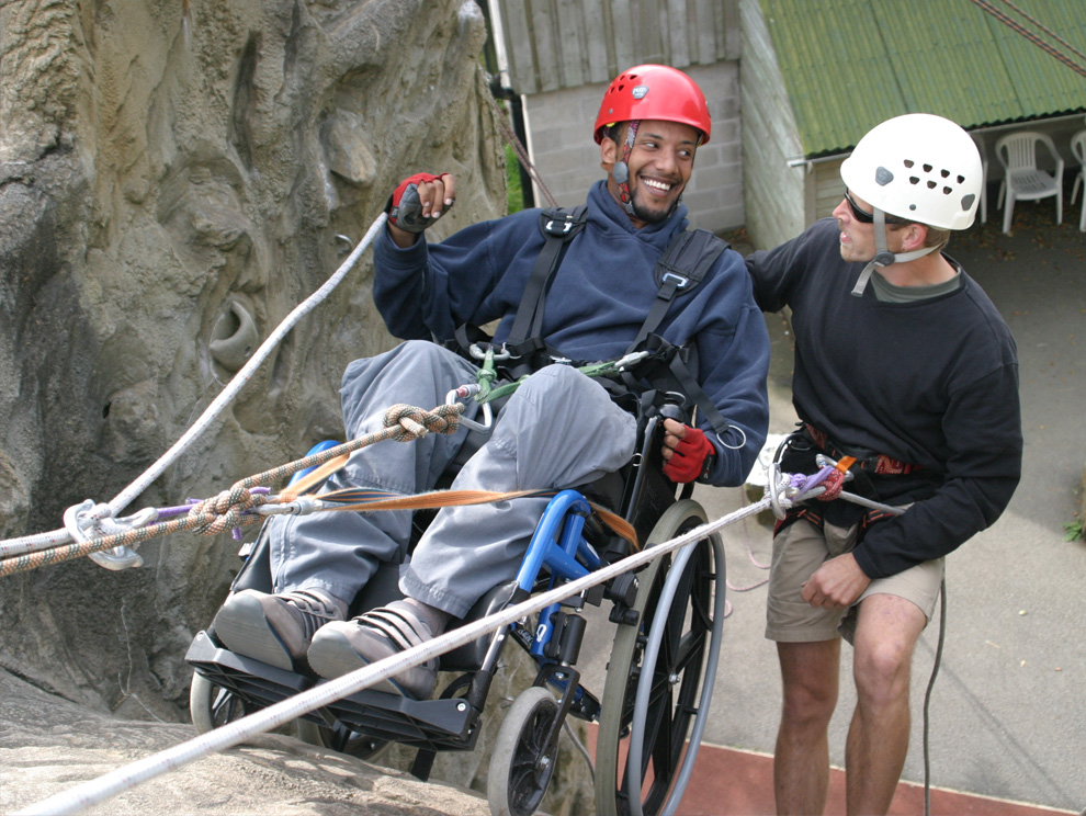 Man in a wheelchair abseiling down outdoor climbing wall with another man using specialised harness, slings and safety ropes