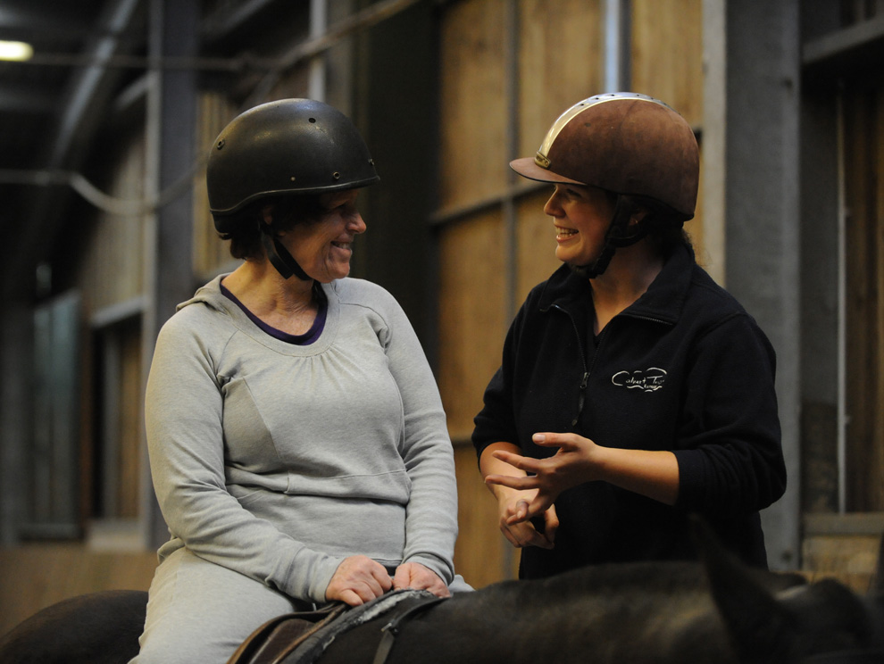 Lady on a horse chatting to a horse riding instructor in an indoor menage
