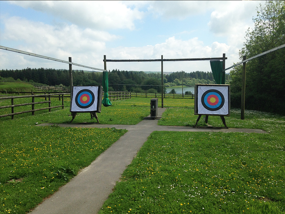 Two archery targets in outdoor range with grass, water and tress in the background