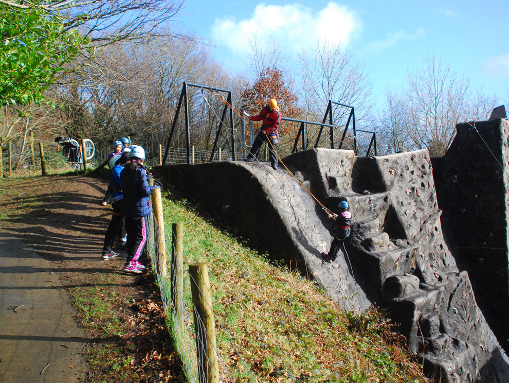 Child abseiling down an outdoor climbing wall with ropes and an instructor, with people watching, all wearing helmets