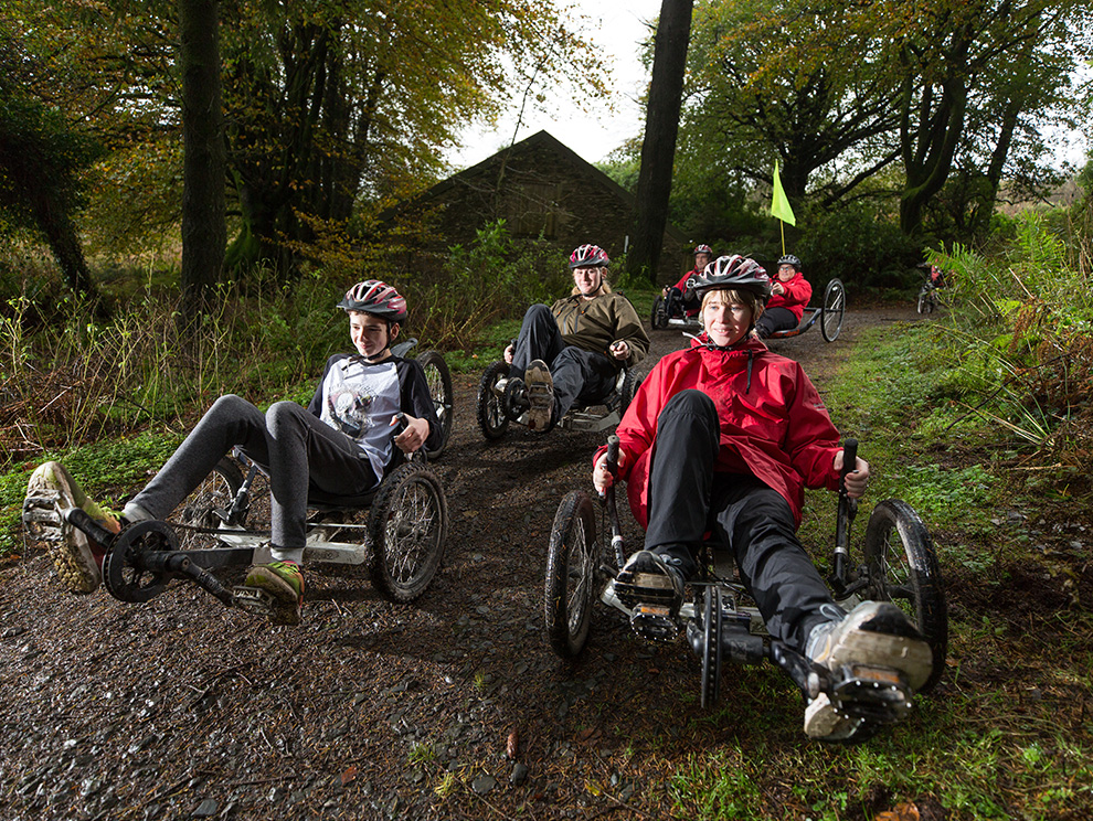 Group of people cycling in recumbent bicycles along a dirt track