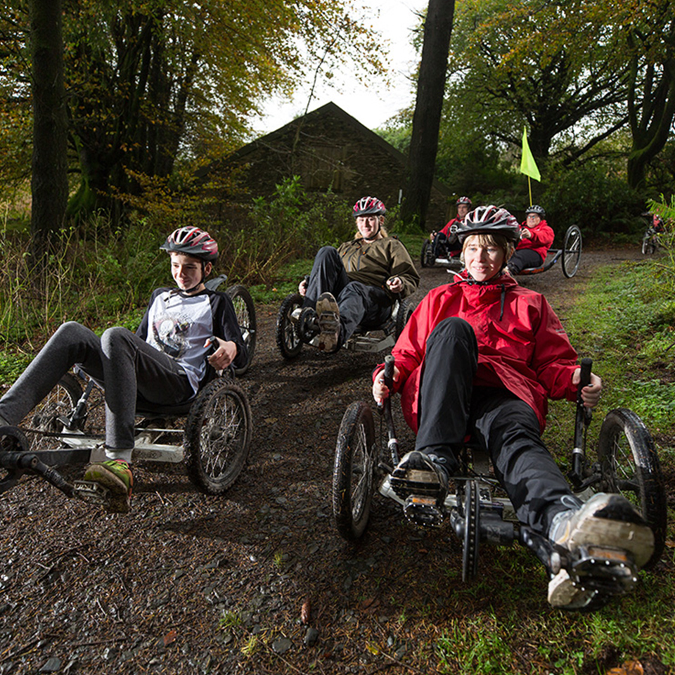 Group of people wearing helmets riding specialised recumbent bikes along a dirt track