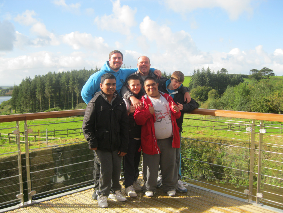 A group of people posing for the camera on a veranda in front of a green scenic background