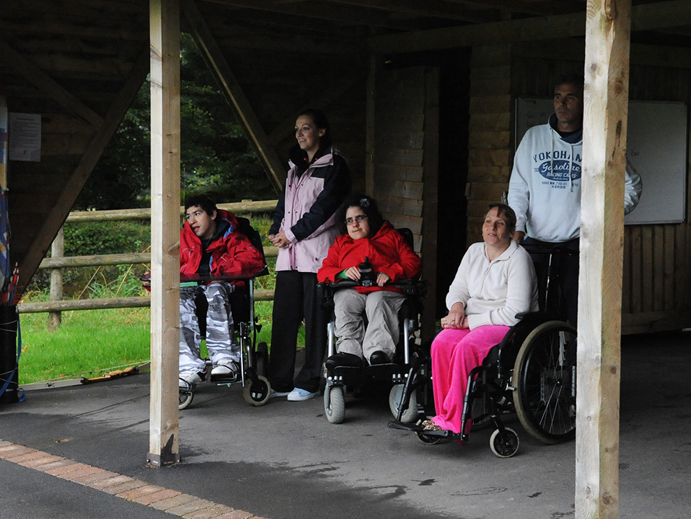 A group of people, some in wheelchairs, watching an activity under a shelter