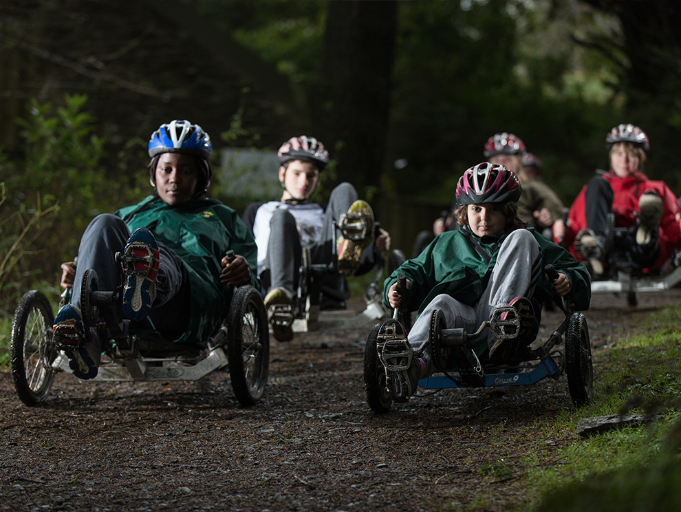 Group cycling in specialist recumbent bikes along a dirt track