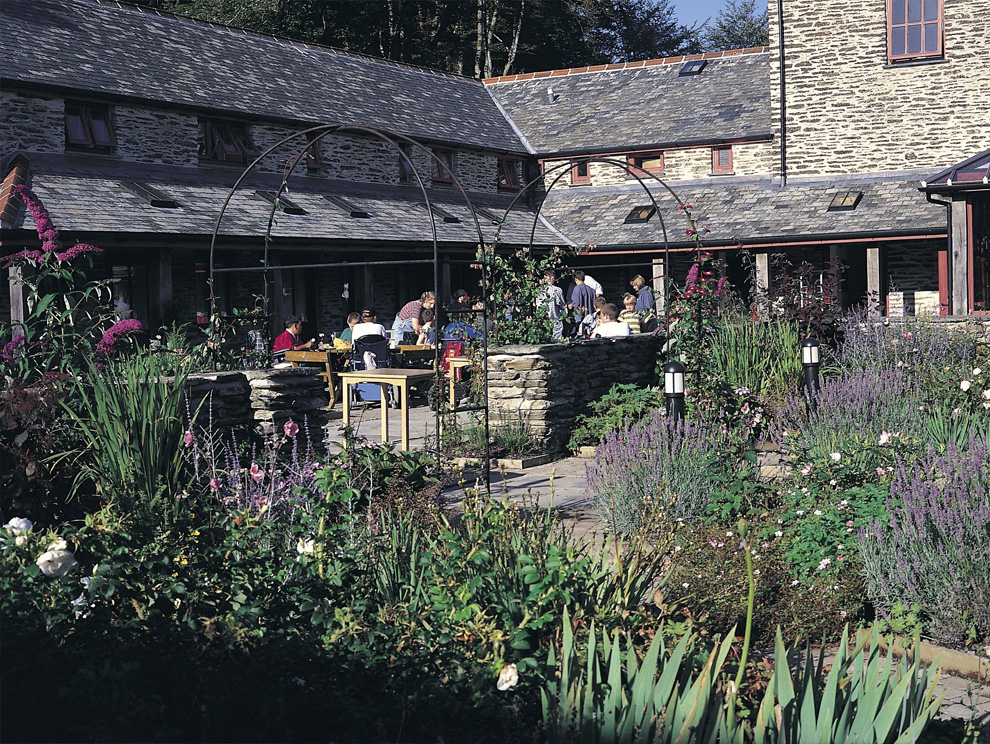 Group of people sitting at outside tables in a courtyard with flowers and plants, surrounded by a stone building