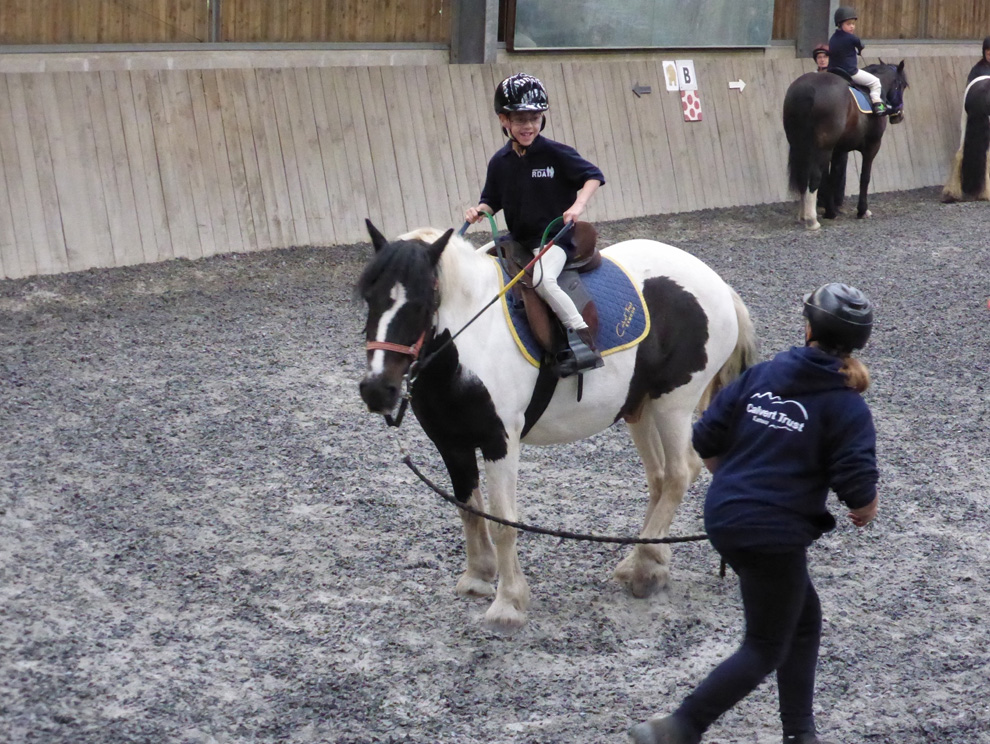 Child riding a brown and white horse in an indoor arena, being led by a rope, learning to steer, with other people and horses in the background