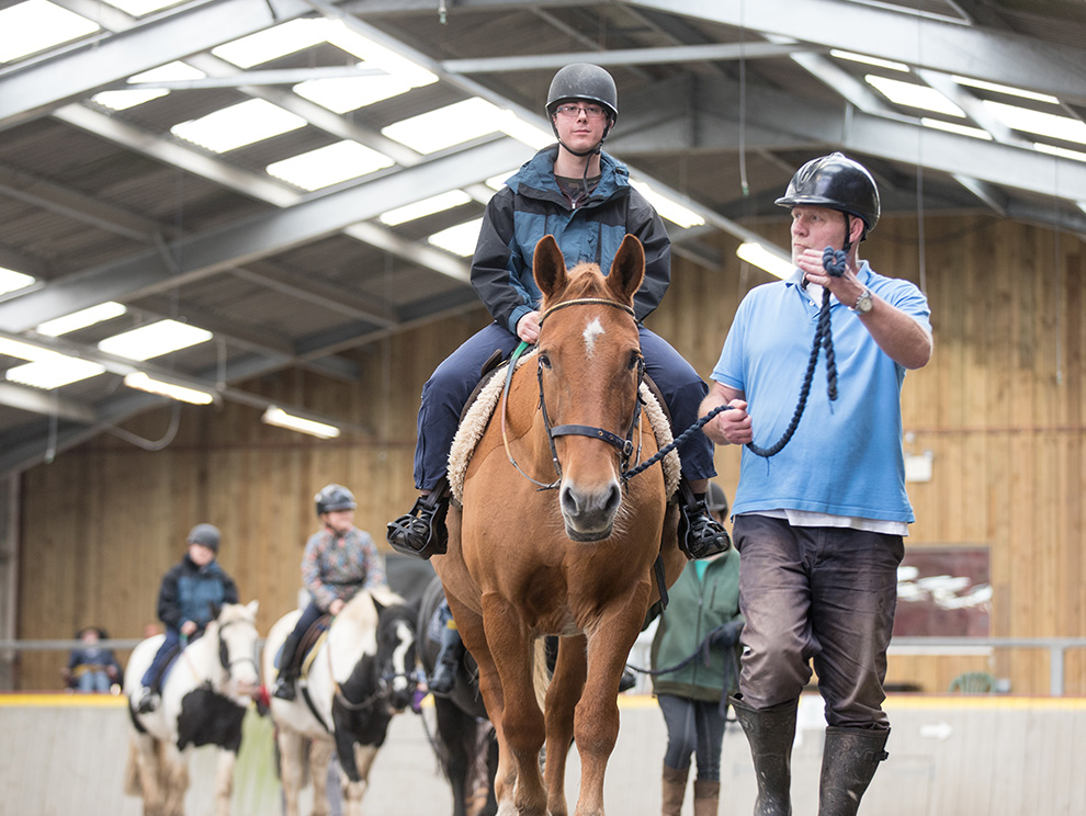 A line of horse riders riding in an indoor arena with volunteers helping to lead horses