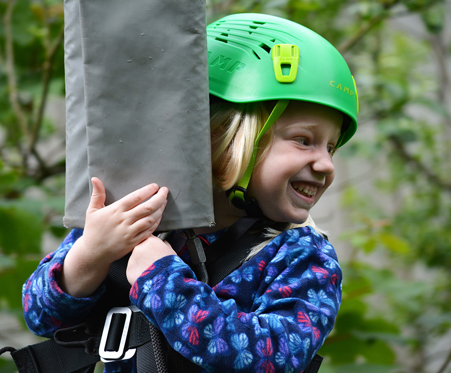 Young girl smiling and looking away, wearing a green helmet, holding onto zipline harness with trees in background