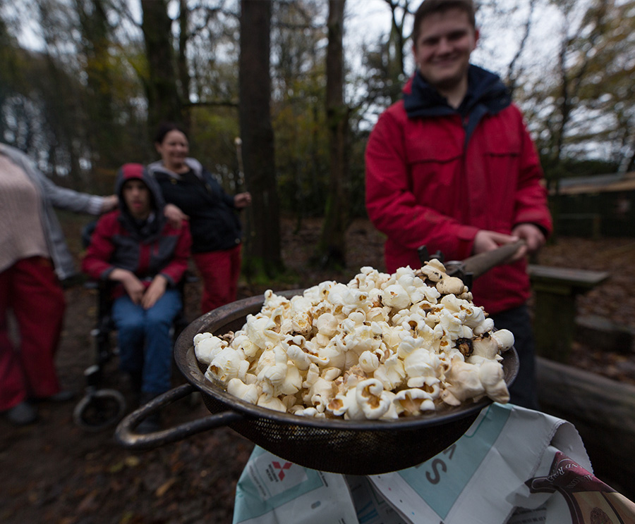 Popcorn being cooked in a sieve over a campfire in the woods