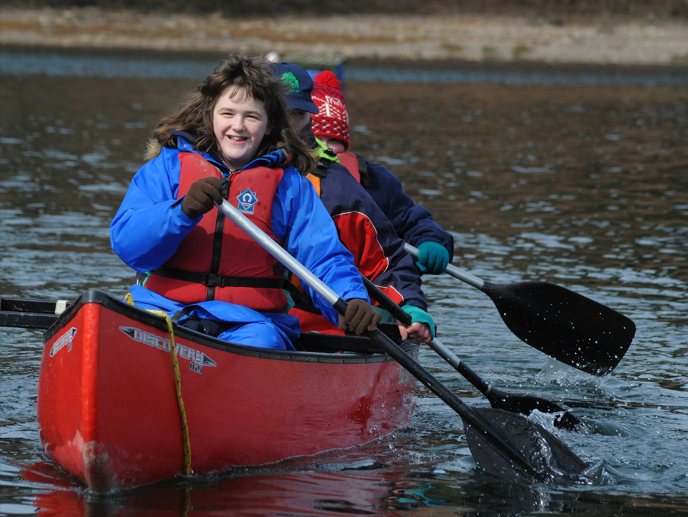 Three people in a canoe paddling on the water looking happy