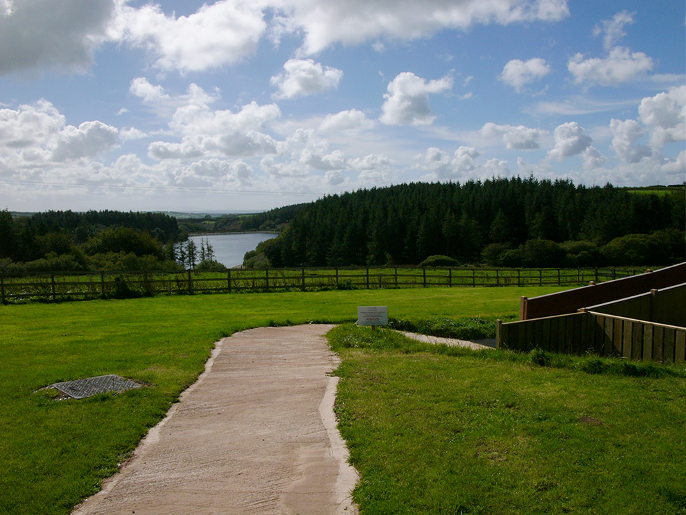 View of Wistlandpound Reservoir, water surrounded by trees and green countryside, with blue sky and fluffy white clouds