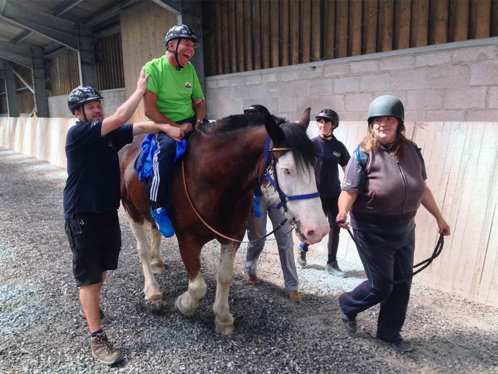 Disabled guest laughing, riding a dark brown horse in indoor arena with riding instructors and volunteers helping and guiding