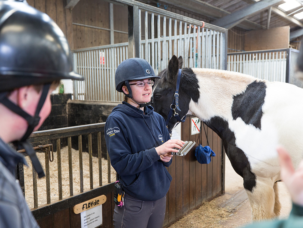 Horse riding instructor standing next to a black and white horse in a stables talking to guests